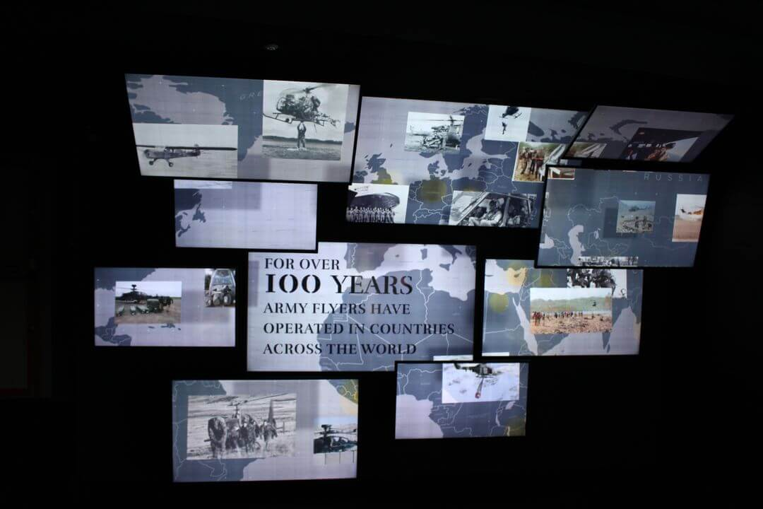 A bank of screens showing pictures and the text 100 years of army flying.