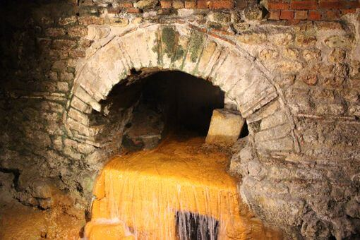 Water gushing out of a brick drain which is stained orange.