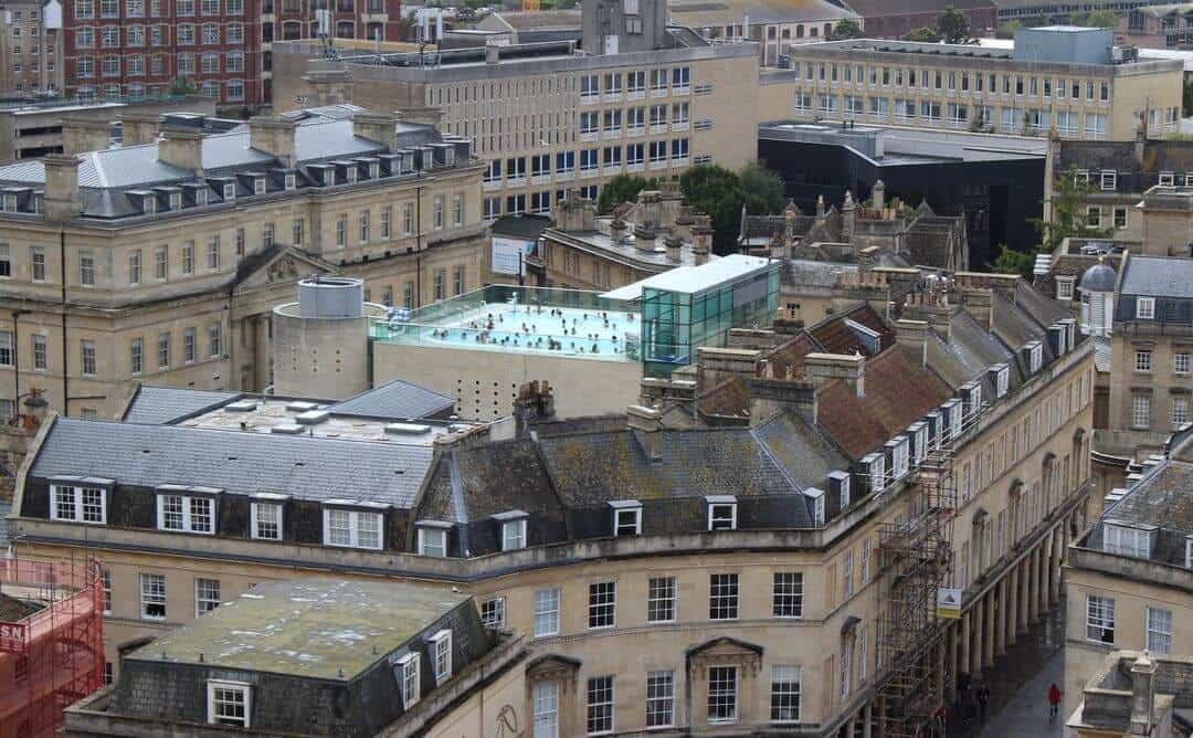 A view over the rooftops of Bath showing an open air pool on top of one of them.