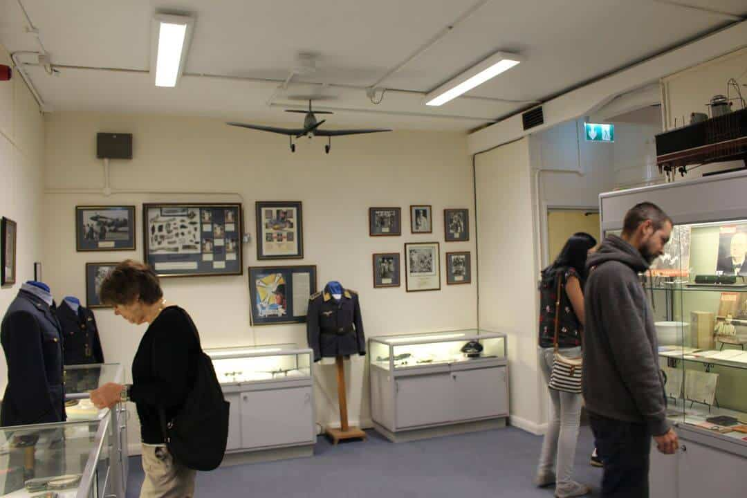 People looking in glass cases in the museum above the Operations Room.