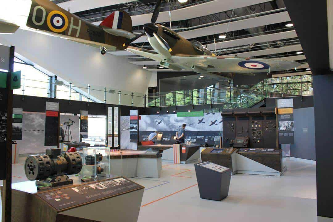 The museum with a plane hanging from above and lots of exhibits.