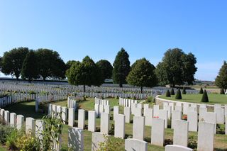 White graves in a circular pattern with trees and blue sky.