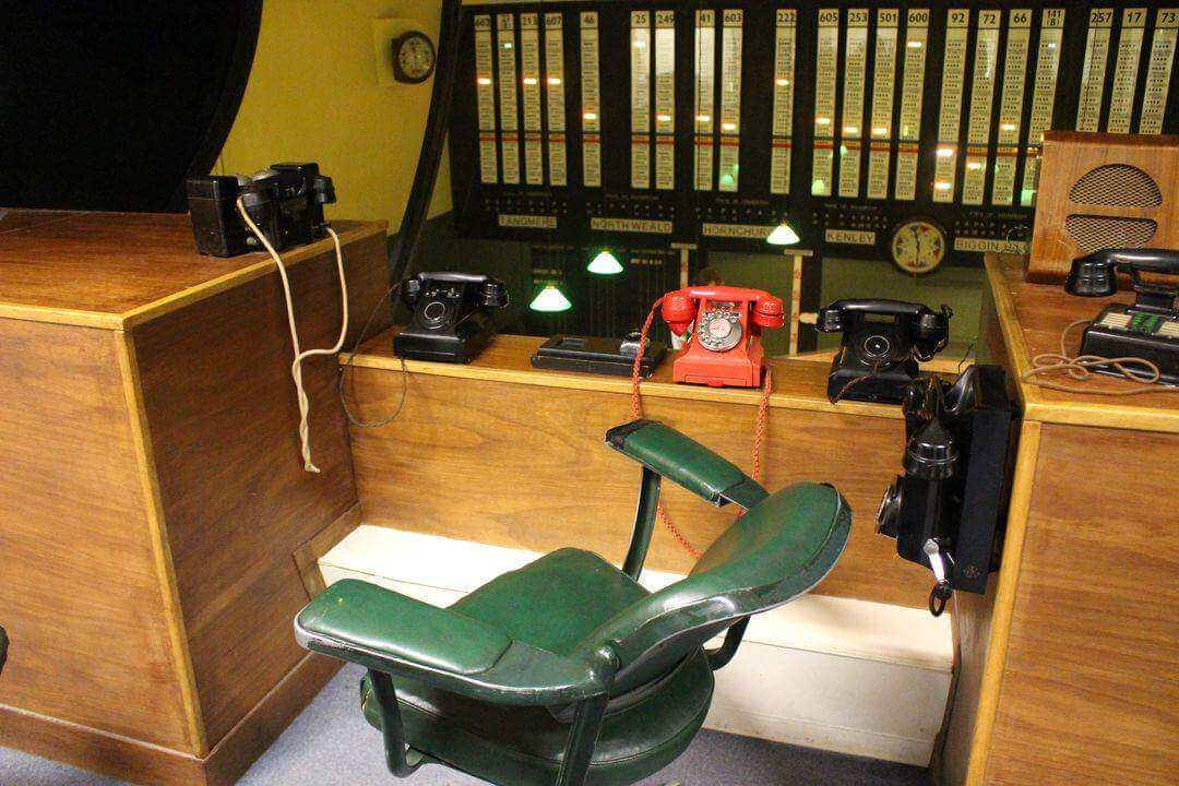 An empty chair in front of a bank of telephones overlooking the Operations Room in the bunker.