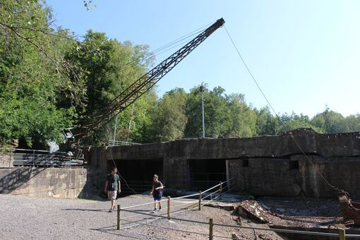 An old crane next to the remains of the concrete bunker.