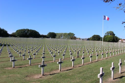 Hundreds of crosses in a grassy cemetery with a French flag flying above them.