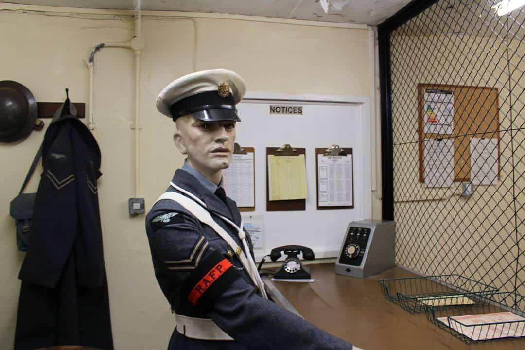 Mannequin at entrance ot bunker in RAF uniform .