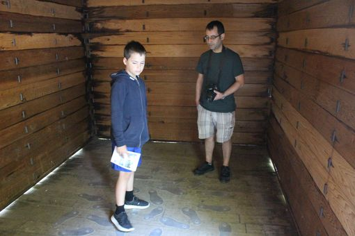 A man and a boy standing inside a wooden train carriage which has footprints on the floor.
