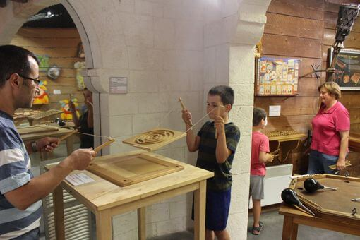 Families playing medieval wooden games inside the museum.