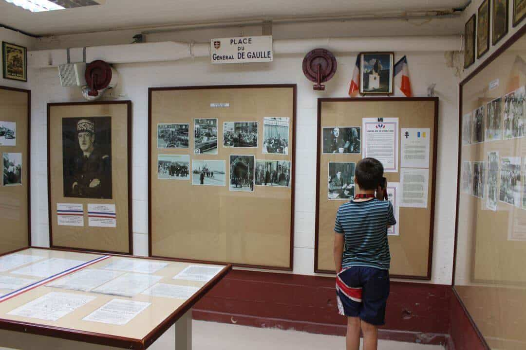 A boy looking at a display case in the Calais Museum.