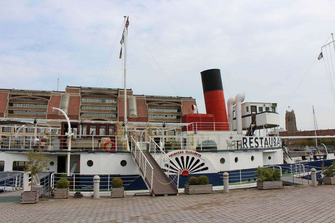 A paddle steamer at dock in front of a tall building.