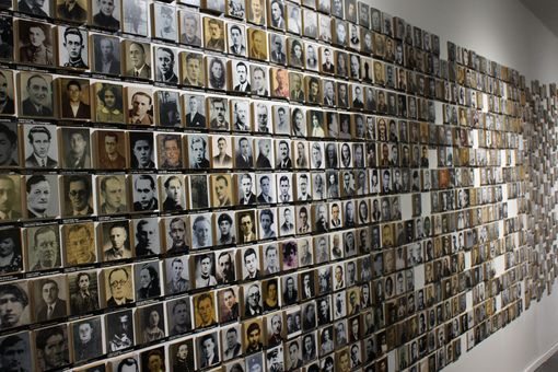 A wall of black and white photos of faces.