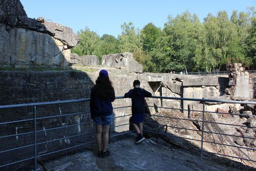 Two children looking at the ruins of a large concrete blockhouse.