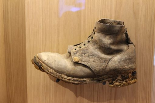 A soldiers boot from World War 1 in a glass case.