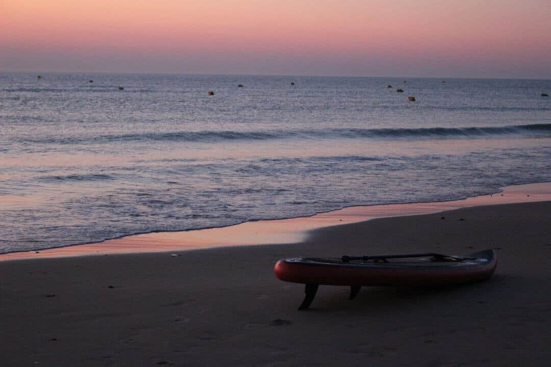 A surboard on a beach in a pink sunset.