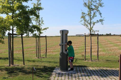 A boy looking through a type of telescope over fields against a blue sky.