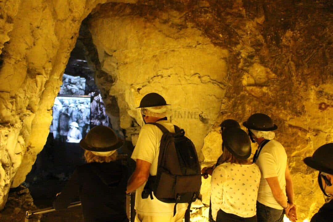 A tour group looking at a film through a gap in rock tunnels.