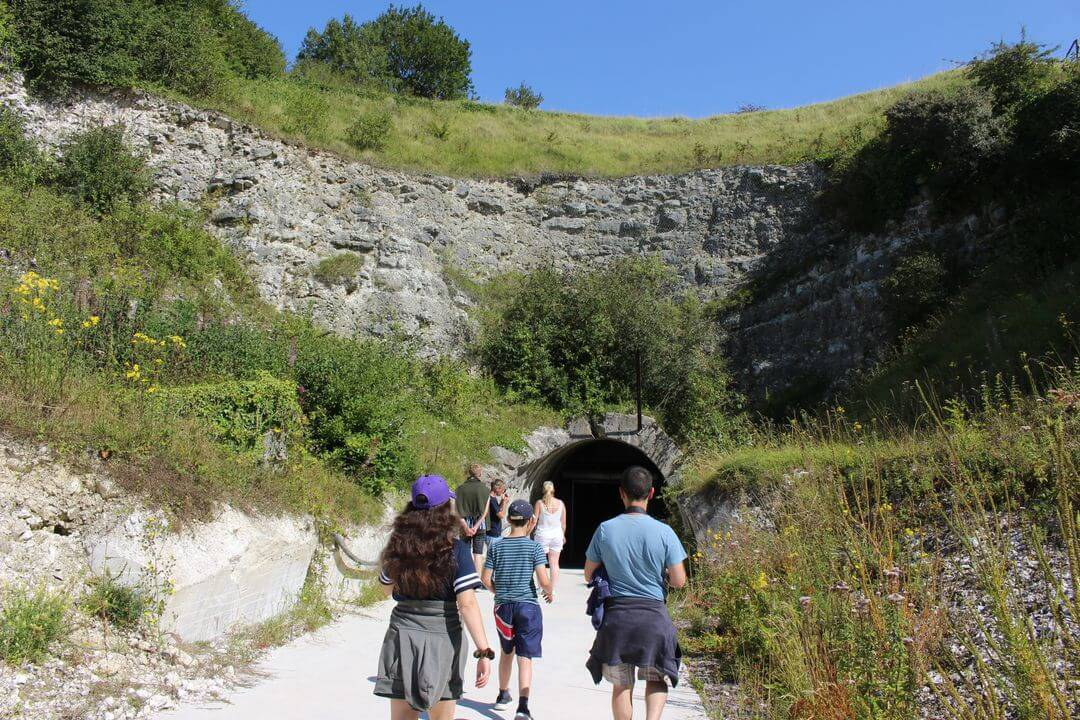 the tunnel entrance in a cliffside with peopke walking towards it.