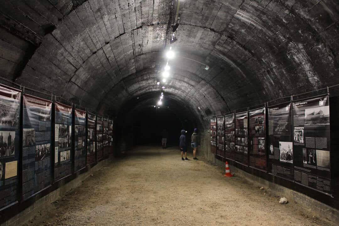 two children at the end of a dark tunnel reading information boards.