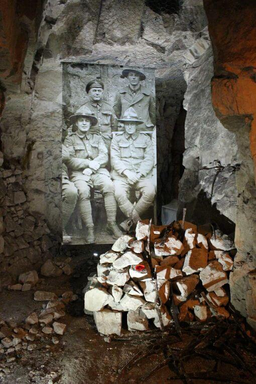 A pile of rocks in front of a picture of WW1 soldiers in a tunnel.
