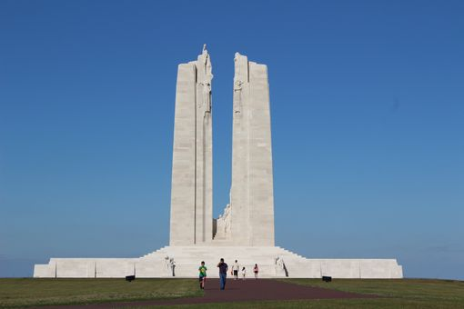 The two white marble columns of the Vimy Ridge Memorial against a blue sky.