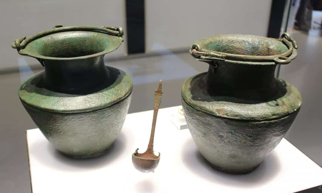 Two bronze wine carriers now green with age in a museum case and with a small ladle in front of them.