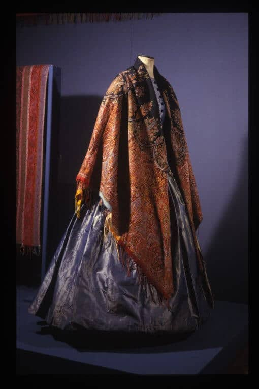 A mannequin wearing a hooped dress with a large colourful shawl.