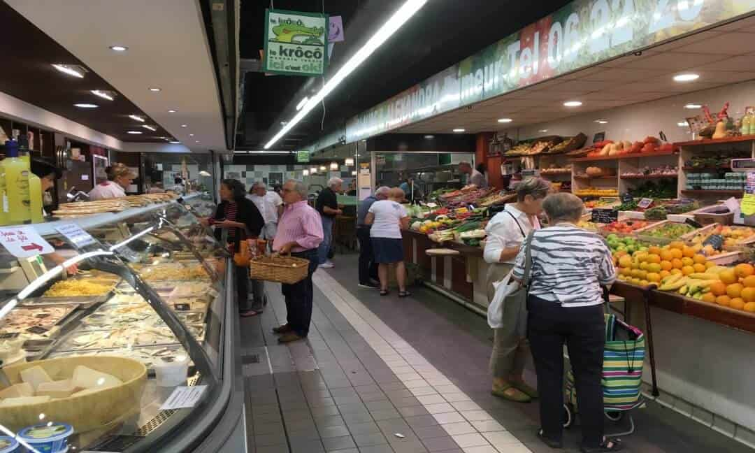 Inside a food market with people shopping at stalls.