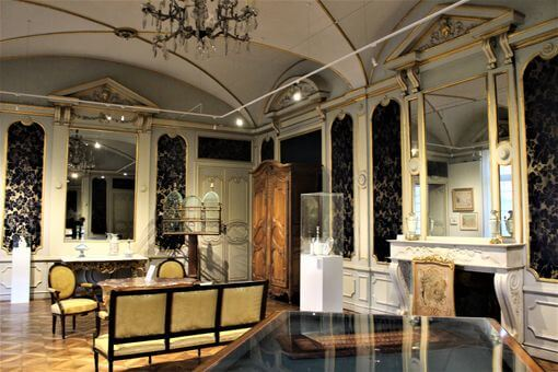 Inside a highly decorated room with objects in glass cases and 18th century furniture.