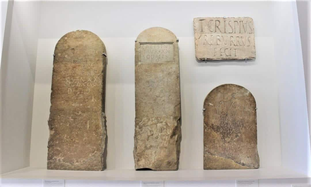 Four stones, three look like gravestones and one plaque in a glass display case in the Musee Romanity in Nimes.