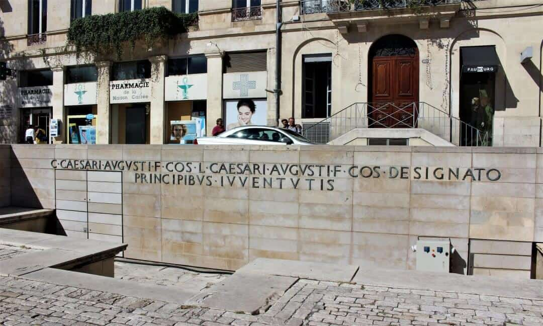 Bronze letters forming Latin words on a low wall in Nimes.
