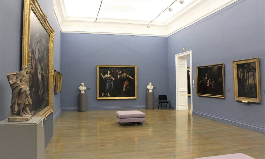 Inside an art gallery with paintings on the walls.