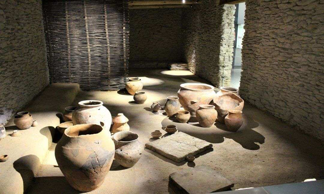 An assortment of pots and amphora inside a replica iron age house.