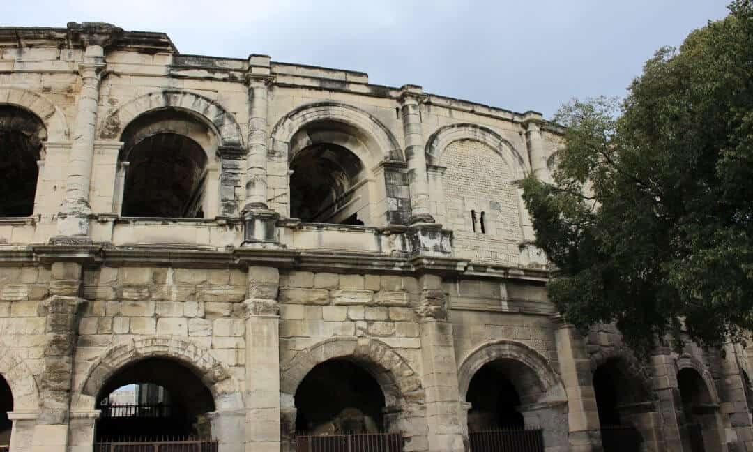 The Arena in Nimes with one of the arches bricked up with a slit window in it.