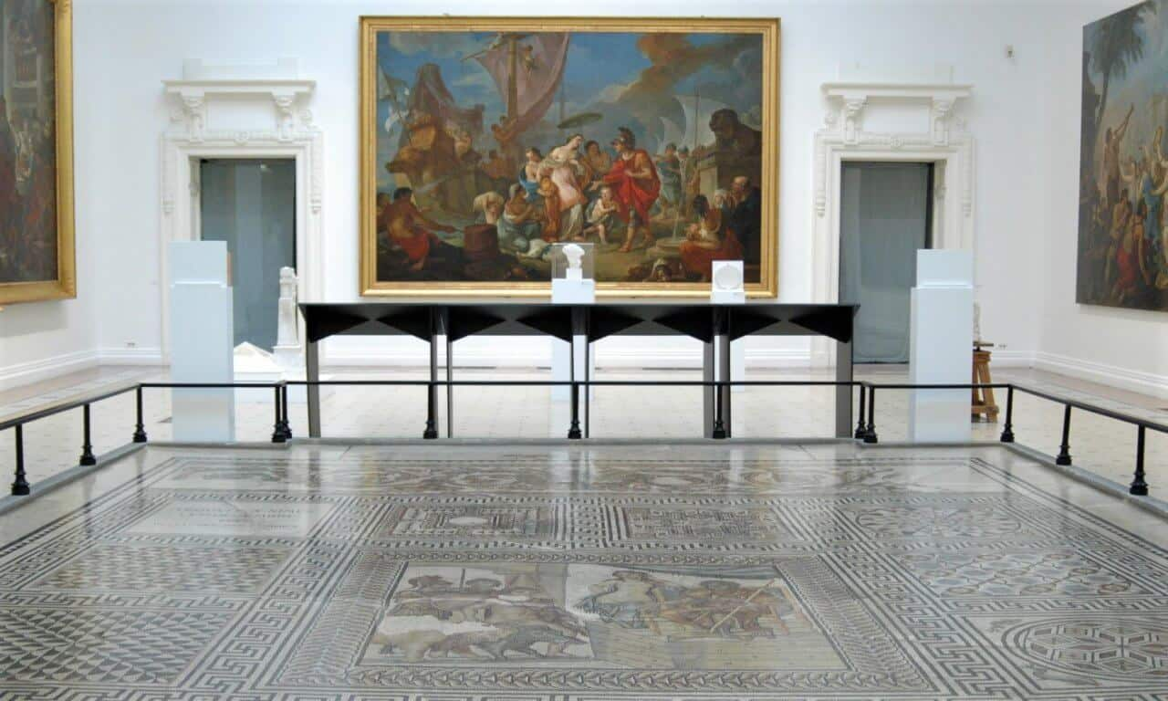 A large mosaic on the ground with a painting on the background wall.