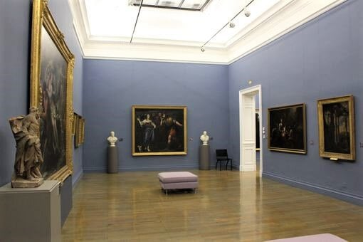 One of the galleries inside the Musee Beaux Arts showing paintings on the wall and a bench in the middle of the room.