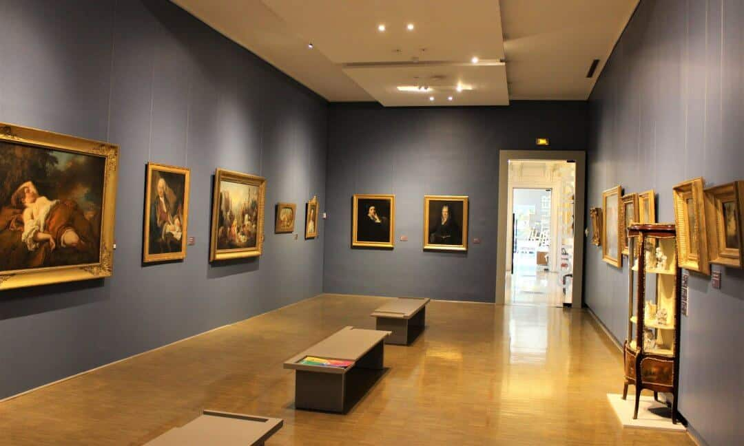 The interior of the Museum of fine Arts showing paintings on the wall and seating in the middle.