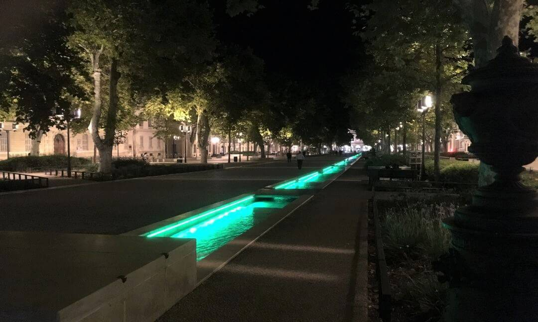 A boulevard at night with an illuminated water channed running down it.