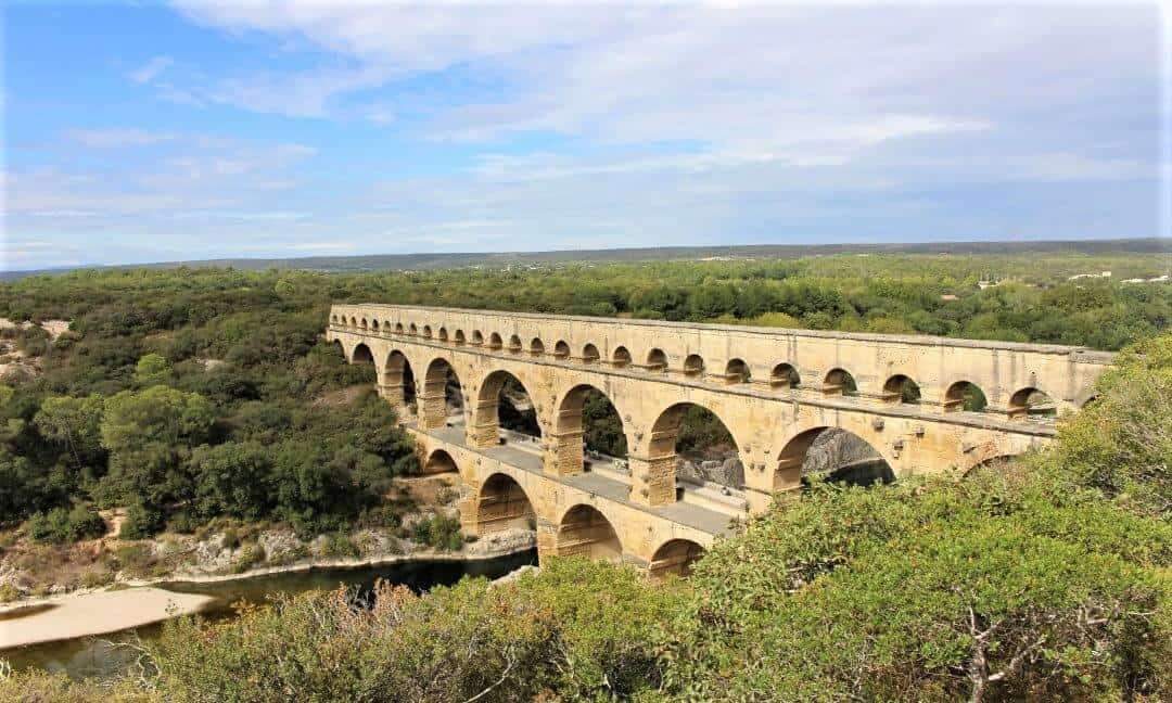 The Pont du Gard bridge and aqueduct against a blue sky.