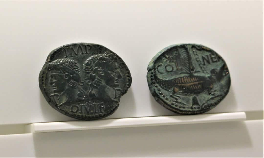 Two Roman coins each showing a different side of the same coin.