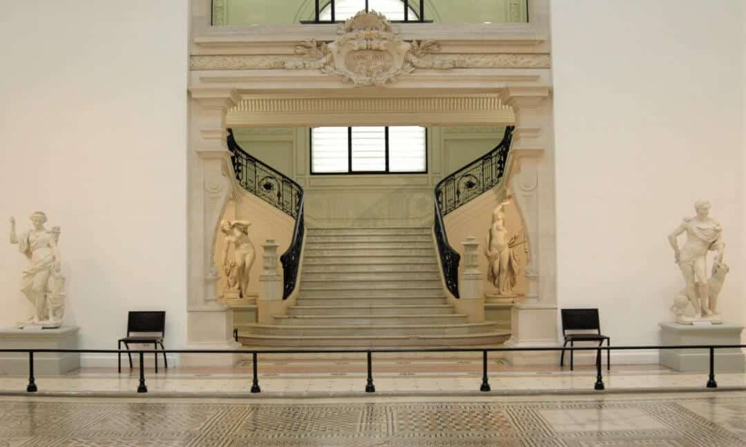 A white marble staircase flanked by two statues in the Museum of Fine Arts in Nimes.