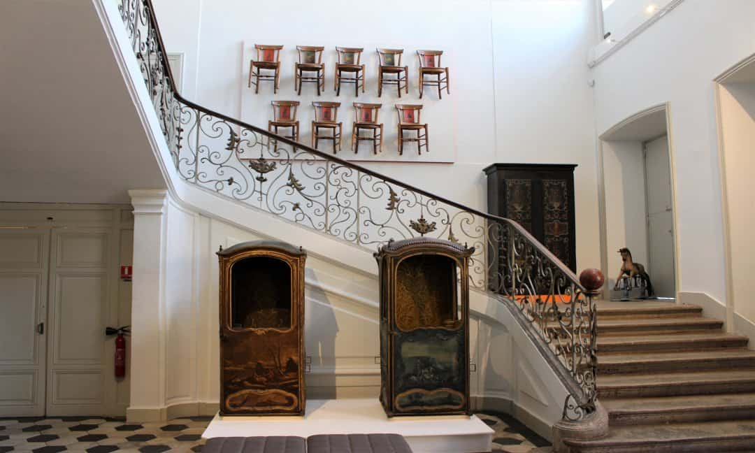 The staircase inside the museum with two sedan chairs in front and chairs attached to the back wall.