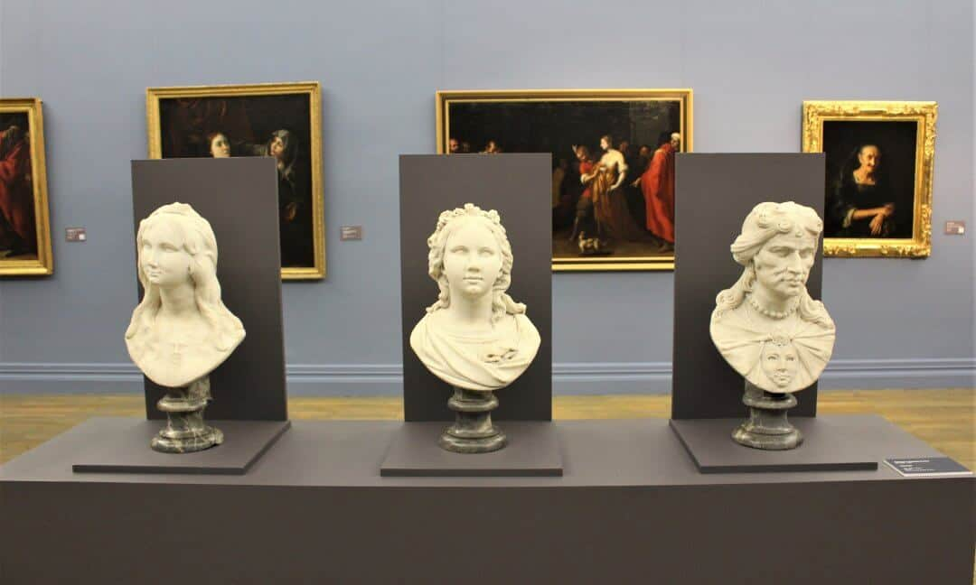 Three white marble busts in an art gallery.