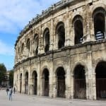 The amphitheatre in Nimes against a blue sky.