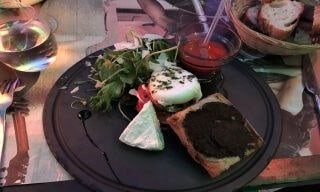 A tomato and mozzarella salad on a table with a basket of bread and a glass of wine.