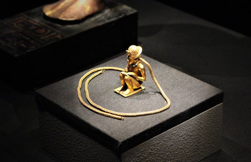 A gold pendant and chain with a carved figure of Amenhotep III.