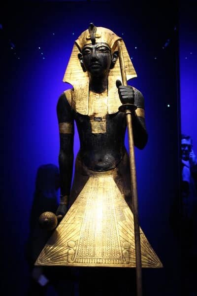 A tall statue of Tutankhamun in black.