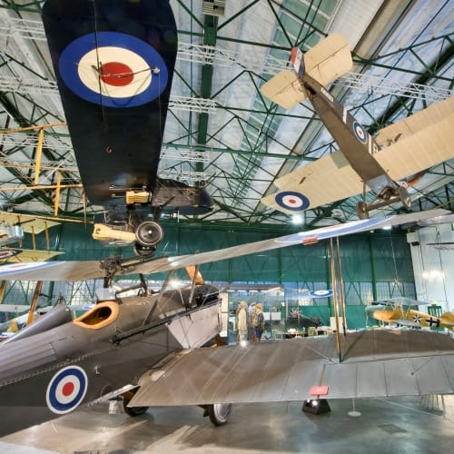 Inside an aircraft hangar showing WW1 planes.