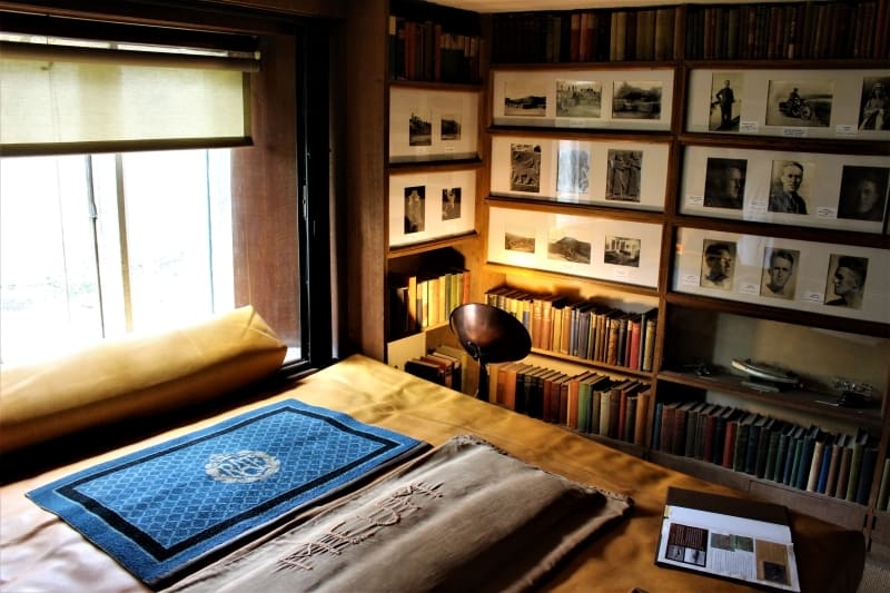 Inside the book room at Clouds Hill showing the the large bed and bookshelves.