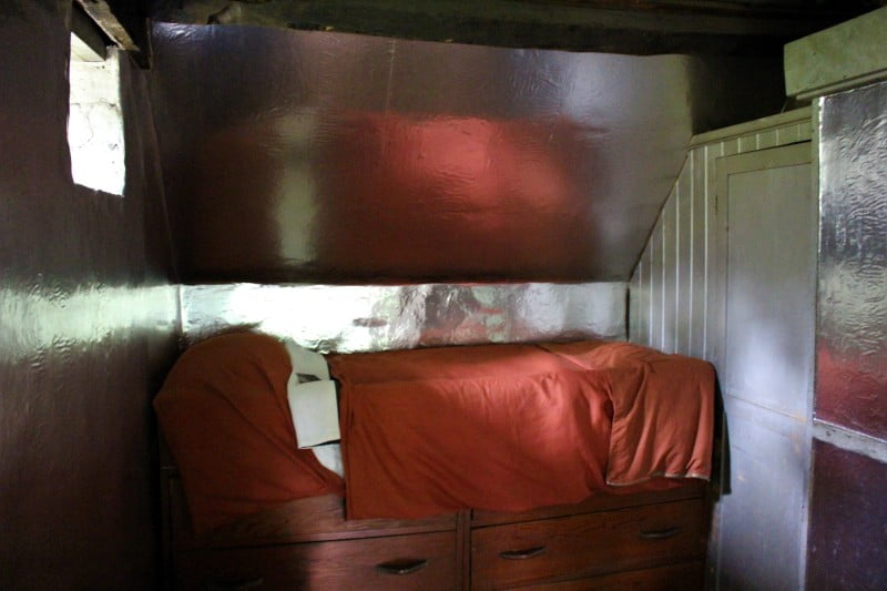 Inside the bunkroom at Clouds Hill showing the silver walls and a wooden cabin bed.