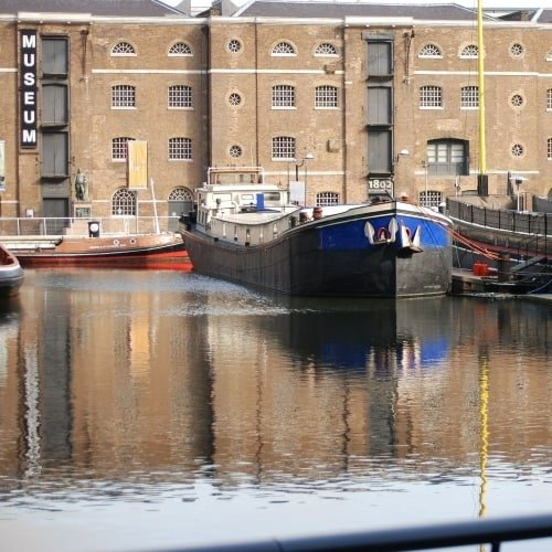 The brown buildings of Canary Wharf and boats in front at the Docklands Museum.